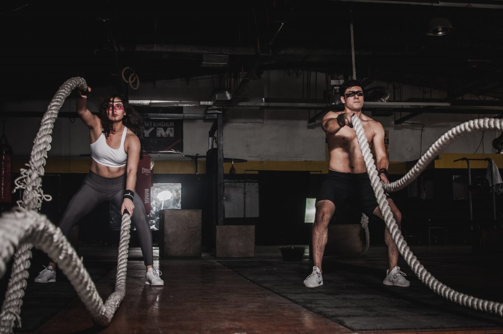 Man and woman working out with ropes